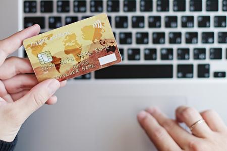 作物は、ラップトップでオンライン購入している間クレジット カードを保持している女性の上から撮影。 写真素材