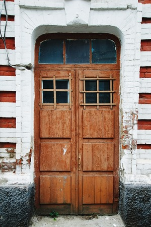 residence: View of shabby wooden doors in white and red brick wall outside.