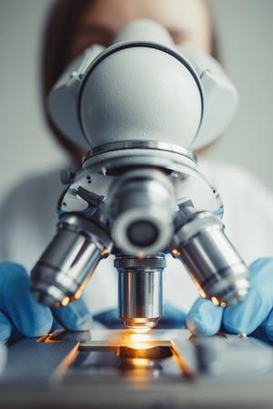 実験室での顕微鏡下での試験試料の検査をクローズアップ。