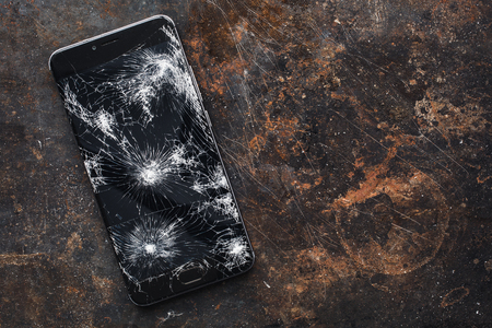 Modern smartphone with large broken screen with debris on the grunge backgdound with copy space