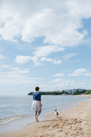 Woman walking with her dog breed Jack Russell Terrier on the sandy beach. No shoes on the water on a Sunny summer day. Rear view.