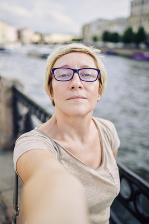 Senior female in glasses looking at camera while taking selfie on embankment of amazing city Stock Photo