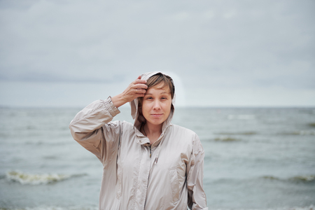 Lovely young lady holding hood of warm jacket and looking at camera while standing on background of waving sea on windy day