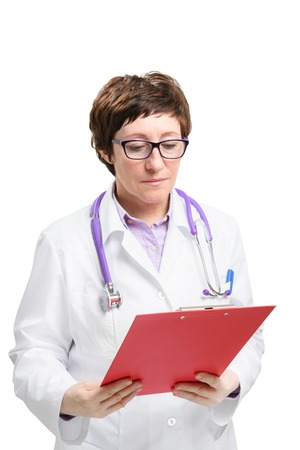 Adult experienced woman doctor with stethoscope loot at clipboard. Isolated on white background. Stock Photo