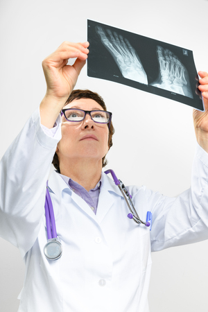 Adult female doctor looking at x-ray of foot Stock Photo