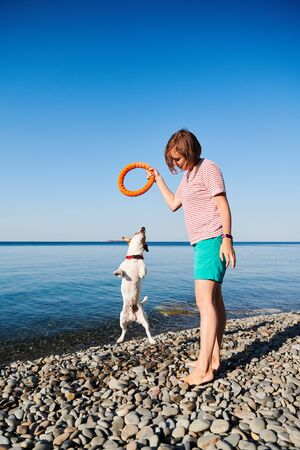 Woman play with her dog on sea coast