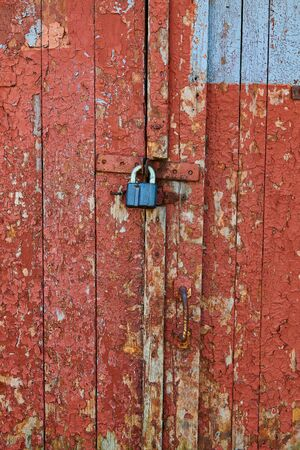 Wooden surface with cracked red paint texture and lock