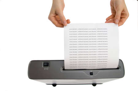 shredder machine: hand and confidential documents into a paper shredder  Stock Photo