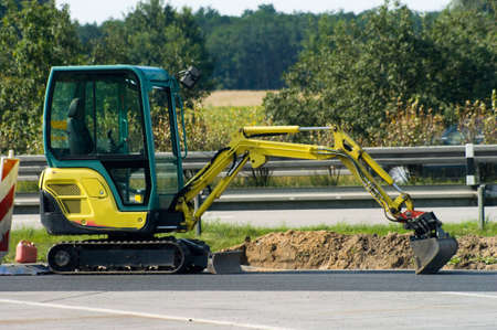 yellow mini excavator on  motorway