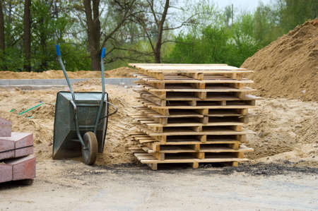 stack of wooden pallets  Barrow at an outdoor construction site  Stock Photo