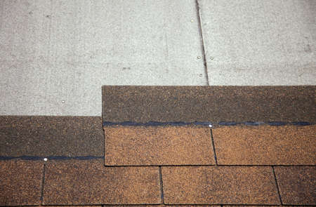 asphalt shingles: A close-up of brown toned architectural style asphalt roofing shingles.  Stock Photo