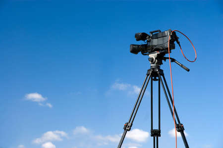 Professional digital video camera on tripod, on blue sky background