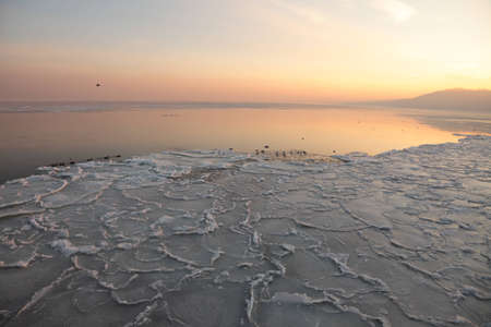 low tide: yellow Sunset on the sea - ice - floe. Poland, Gdynia