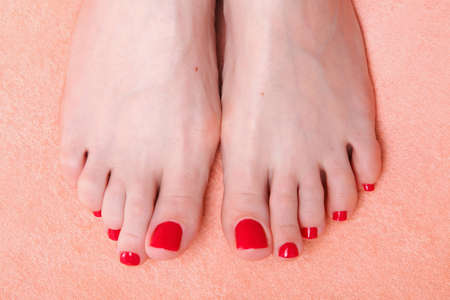 woman feet with red toenails on pink towel Stock Photo - 9700116