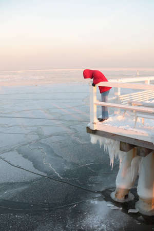 Women in red. Pier, jetty  on the sea - ice - floe. Poland, Gdynia photo