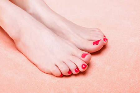woman feet with red toenails on pink towel Stock Photo - 9808002
