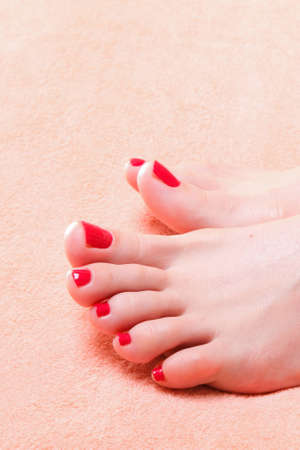 woman feet with red toenails on pink towel photo