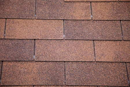 A close-up of brown toned architectural style asphalt roofing shingles.  Stock Photo