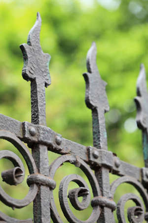 steel picket fence on green background photo