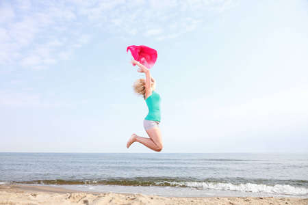 Jumping and dancing happy girl on the beach woman vacation, summertime fun concept photo