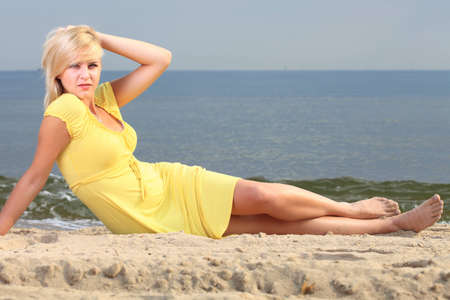 Romantic Beautiful smiling girl in the yellow dress water beach photo