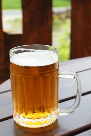 One glass of the light beer on the wooden table in the garden