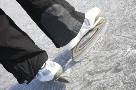 Young woman ice skating outdoors on a pond on a freezing winter day - detail of the legs Stock Photo
