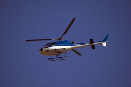 medium close up: A blue helicopter in flight. Medium close up against a blue sky. Stock Photo