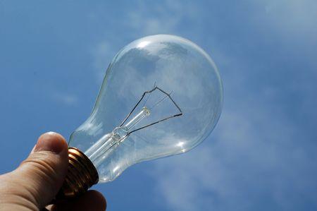 Light bulb held in left hand on blue sky background