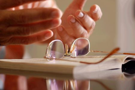 Book, glasses and hands Stock Photo