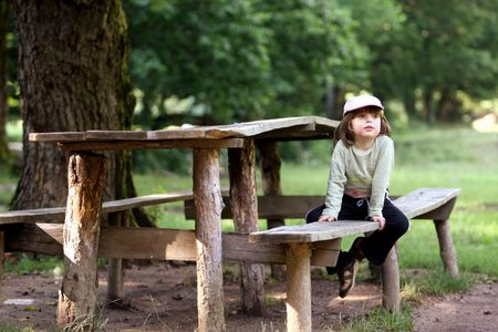 Little girl resting while being on a trip in the woods