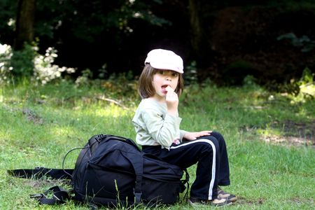 Little girl eating while being on a trip in the woods