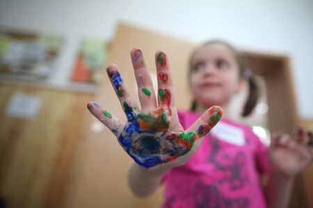 Little girl with colored hands Stock Photo
