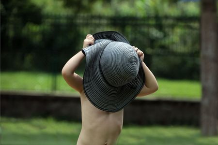 Little boy playing with his mothers hat on a warm summer day. Stock Photo