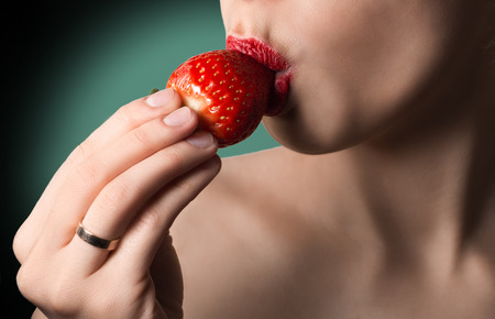 nudity: Sexy image of red lips kissing strawberry. Passion and desire. Perfect skin. Natural nudity and green background.