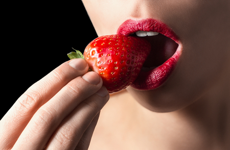 provocative food: Sexy lips eating strawberry. Passion and desire. Strawberry and lips are red. Sexy and nude on black background. Sexy lips, white teeth, delicious strawberry.