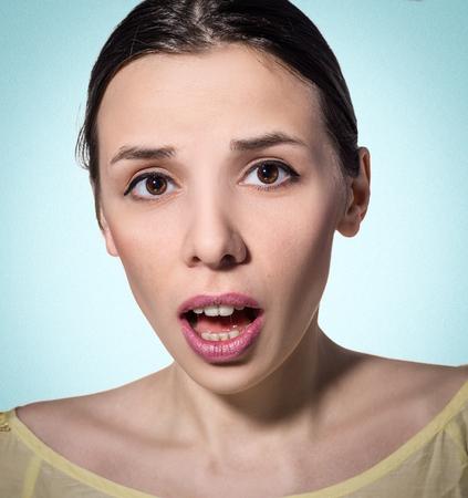 asombro: Mujer desconcertada y sorprendida. fondo azul. natural de la piel y maquillaje. Foto de archivo