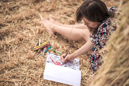 colorful dress: relaxation. the girl sitting on the hay and coloring, with different bright pencils, colorful dress and slim legs