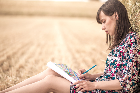 beautiful smile: the brunette sitting on the hay and coloring, with different bright pencils and slim legs and hat. beautiful smile