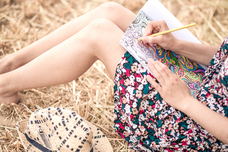 colorful dress: sitting on the hay and coloring, with different bright pencils, colorful dress and slim legs and hat Stock Photo
