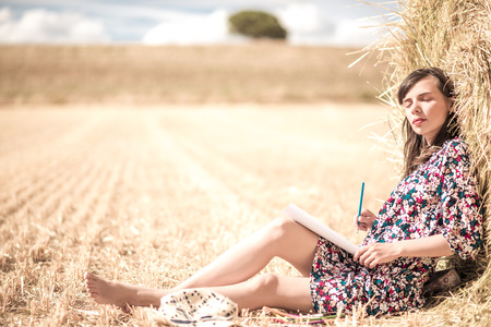 closed eyes: the brunette sitting on the hay and coloring, with different bright pencils and slim legs and hat. closed eyes