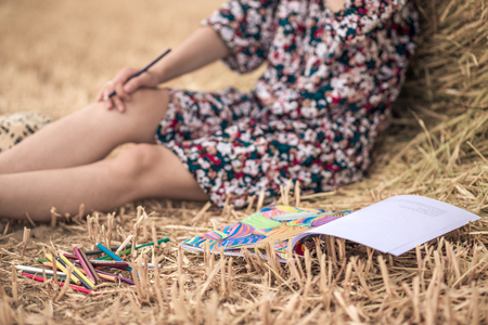 colorful dress: the girl sitting on the hay and coloring, with different bright pencils, colorful dress and slim legs and hat