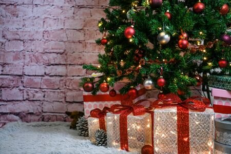 christmas tree and xmas gifts in front of brick wall background with negative space