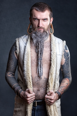 A man with a long beard and tunnels in the ears with tattoos  photo