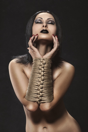 Glamour girl with dark make-up and tied his hands in bondage  photo