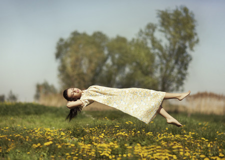 weightlessness: Girl in pajamas night flying over the field and dreams