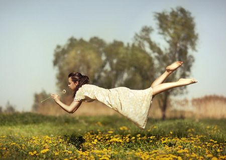 Girl in pajamas night flying over the field and smelling dandelions
