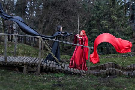 Mädchen in einem roten Vintage Kleid schlägt Schwerter Mädchen im schwarzen Kleid alt Standard-Bild - 26549263