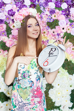 horologe: Girl with a wreath of flowers on her head pointing the finger at the clock