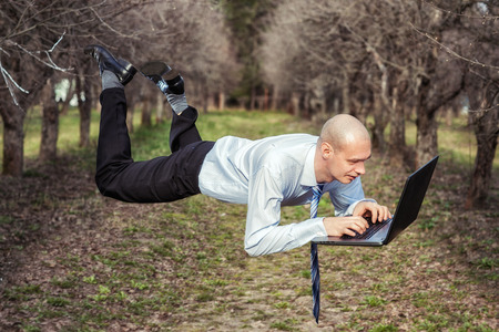 levitating: Man flies and works for laptop  Stock Photo